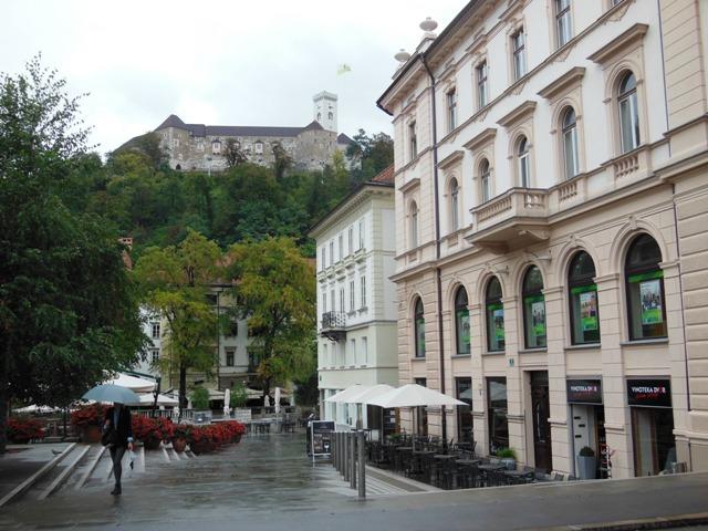Straatbeeld van Ljubljana met de typische Art-Nouveau bouwstijl. Op de achtergrond het Ljubljana Castle op de heuvel.